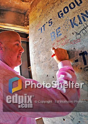 """9 June 2012: Washington Nationals General Manager Mike Rizzo signs the wall inside the famed """"Green Monster"""" scoreboard wall with the message: """"See You Guys in the World Series"""" prior to a game against the Boston Red Sox at Fenway Park in Boston, MA. The Nationals defeated the Red Sox 4-2 in the second game of their 3-game series. Mandatory Credit: Ed Wolfstein Photo"""
