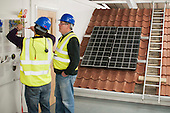 Electricians updating their skills in the Renewables section at the Able Skills Training Centre, Dartford, Kent.  Behind them, a set of photovoltaic panels which turn solar rays into electricity.