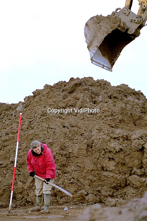 Foto: VidiPhoto..OOSTERHOUT - Medewerkers van de dienst Archeologie van de gemeente Nijmegen, werken met man en macht in de blubber om voor maandag een Romeinse nederzetting in kaart te hebben gebracht. De werkzaamheden op dit Oosterhoutse stuk van de Nijmeegse Waalsprong liggen nu stil vanwege de winterstop. De twintig archeologen hebben tot maandag vrij spel. Dan wordt begonnen met de aanleg van de riolering. Die komt dwars door de historische nederzetting heen te liggen.