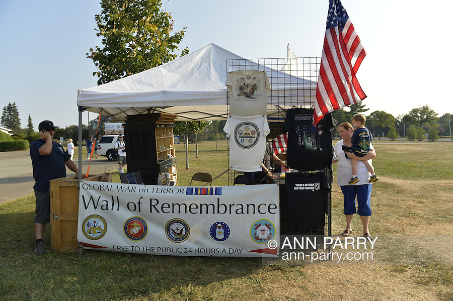 """East Meadow, New York, U.S. 11th September 2013. ROSEMARY HUNTER, of Wantagh, is holding her son TIMOTHY HUNTER, 3. as she speaks with RICHARD NICHOLS at the counter of the booth at the Global War on Terror """"Wall of Remembrance"""" a traveling memorial on display in New York for the first time, at Eisenhower Park on the 12th Anniversary of the terrorist attacks of 9/11. Nicholas began building the wall on 9/11/11, and DEREK HENDERSHOT, at left, is a n assistant. The unique 94 feet long by 6 feet high wall has, on one side, almost 11,000 names of those lost on September 11, 2001, along with heroes and veterans who lost their lives defending freedom of Americans over past 30 years. On the wall's other side is a timeline, with photos, covering 1983 to present day."""