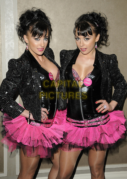 THE CHEEKY GIRLS - MONICA & GABRIELA IRIMIA.Attending the 'Mad Hatters Tea Party' event organised by London Taxi Drivers Fund for Underprivileged Children at the Grosvenor House Hotel, Park Lane, London, England, UK..January 31st 2010..half length twins sisters family black pink tutu matching skirt outfits sequined sequin jacket shoulder pads biker bra pvc shiny top punk  hands on hips badge No Angel slogan tutus .CAP/CAN.©Can Nguyen/Capital Pictures