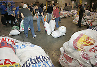 Wednesday, Feb. 15, 2006  Anchorage, Alaska.  Several of the thousands of Iditarod volunteers work to sort and weigh musher food drop bags into stacks to be flown or mailed out to the 20 checkpoints along the trail.   In each bag is food for the dogs and musher as well as fresh equipment for the musher including; sled runner plastic, gloves, batteries, clothing and more.