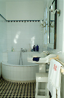 The bathroom has a built-in circular bath and is tiled on the floor and walls