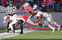 Ohio State Buckeyes running back Ezekiel Elliott (15) goes flying through the air from a tackle by Indiana Hoosiers cornerback Tim Bennett (24) in the fourth quarter of the college football game between the Ohio State Buckeyes and the Indiana Hoosiers at Ohio Stadium in Columbus, Saturday afternoon, November 22, 2014. The Ohio State Buckeyes defeated the Indiana Hoosiers 42 - 27. (The Columbus Dispatch / Eamon Queeney)