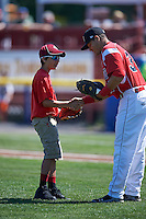 Batavia Muckdogs catcher Roy Morales (34) shakes hands with a young fan after the ceremonial first pitch before a game against the Williamsport Crosscutters on July 16, 2015 at Dwyer Stadium in Batavia, New York.  Batavia defeated Williamsport 4-2.  (Mike Janes/Four Seam Images)