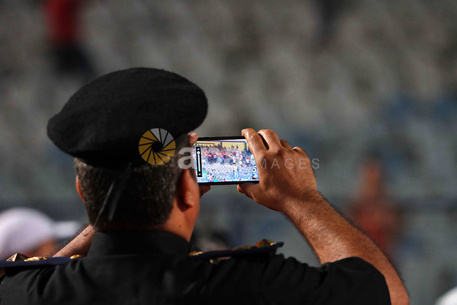 An Egyptian Policeman takes a picture during the qualifying match of 2015 Africa Cup soccer match, in Cairo, capital of Egypt, on Oct. 15, 2014. Egypt won the match with 2-0. Photo by Amr Sayed