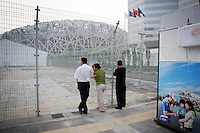"""CHINA. Beijing. People peer through a fence, trying to catch a glimpse of the new Olympic stadium. In recent years construction has boomed in Beijing as a result of the country's widespread economic growth and the awarding of the 2008 Summer Olympics to the city. For Beijing's residents however, it seems as their city is continually under construction with old neighborhoods regularly being razed and new apartments, office blocks and sports venues appearing in their place. A new Beijing has been promised to the people to act as a showcase to the world for the 'new' China. Beijing's residents have been waiting for this promised change for years and are still waiting, asking the question """"Where's the new Beijing?!"""". 2008."""