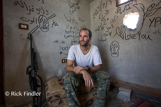 August 2017. Raqqa, Syria.<br /> Foreign volunteer fighter 'Macer Gifford' sits in one of his locations which he uses to fire his sniper rifle targeting ISIS.<br /> The MFS (Syriac Military Council) are a group of Assyrian Christians who fight alongside the Syrian Democratic Forces in the fight to topple ISIS.<br /> Photographer: Rick Findler