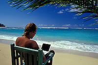 Man working on laptop computer at beach under a palm tree