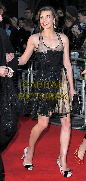 MILLA JOVOVICH .attending Gorby 80 Gala Concert at the Royal Albert Hall, Kensington Gore, London, England, UK, 30th March 2011..full length black mesh dress gold tulle polka dot ruffle lace sleeveless sheer see thru through peep toe beige cream patent bows shoes clutch bag .CAP/BEL.©Tom Belcher/Capital Pictures.