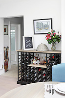 A conveniently placed wine rack has been placed near the table in the dining room