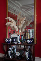 A collection of ceramics is displayed against a large wall-glass in the red drawing room