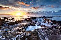 Water cascading off of a rocky shelf under a golden sunset at Shark's Cove, North Shore, Oahu