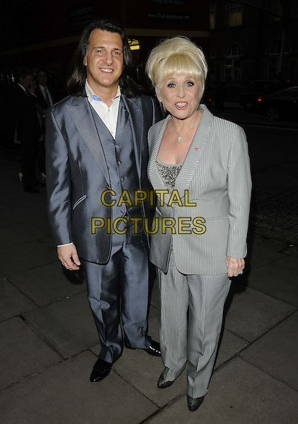 """Scott Mitchell & Barbara Windsor.The """"My Beautiful Ball"""",The Landmark Hotel, London, England..April 11th, 2013.full length grey gray suit  babs silver clutch bag waistcoat married husband wife .CAP/CAN.©Can Nguyen/Capital Pictures."""