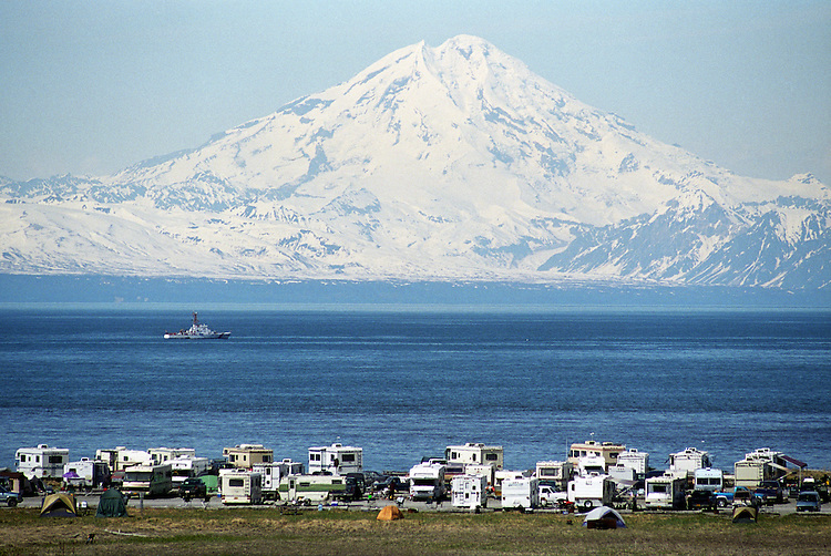 Mount Redoubt rises above campers and recreation vehicles parked at Deep Creek's mouth on the shore of Cook Inlet.