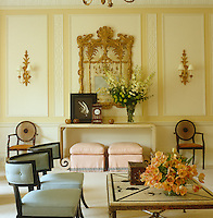 A pair of gilded sconces flanks a gilded mirror on one wall of the formal drawing room with a photograph by Herb Ritts