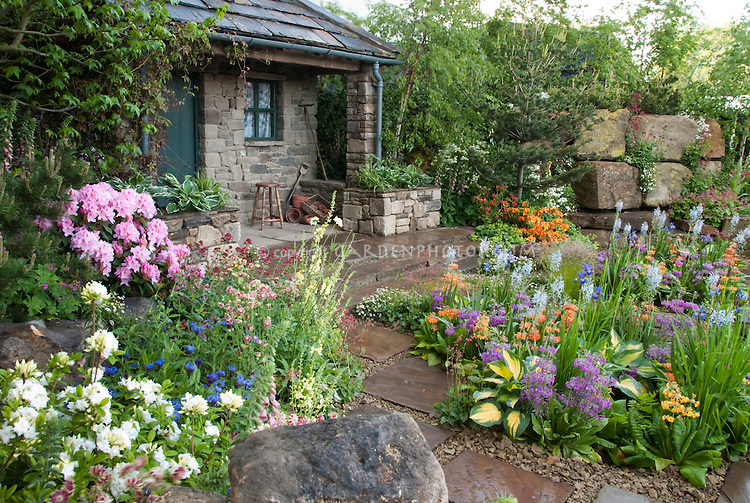 spring flower garden with rhododendrons and azales stone shed or house stone patio and - Flowers For Home Garden