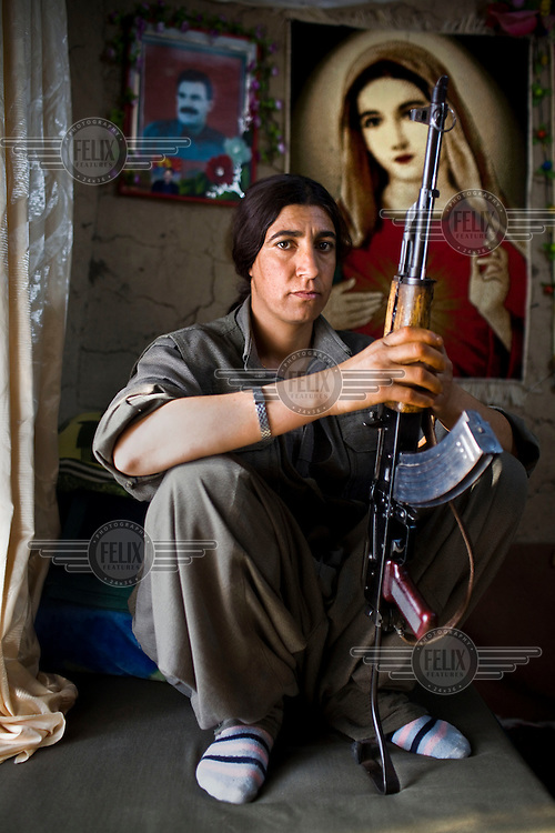 22 year PKK guerrilla Sarya Agiri from Iran poses for a portrait. She has been wioth the PKK for four years. Sarya carries her own gun and her current duty is working at the sewing workshop. Labelled as terrorists by the Turkish, US and EU, it's in the Qandil Mountains near the border where the guerrillas of the PKK (Kurdistan Worker's Party) live and wage their 26 year war against Turkey that has claimed over 40,000 lives.