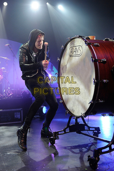 Dan Reynolds of Imagine Dragons.Imagine Dragons performing in concert, The Forum, London, England, UK, 11th April 2013..music live on stage gig full length black leather jacket jeans t-shirt hoodie hood banging drum gong playing .CAP/MAR.© Martin Harris/Capital Pictures.