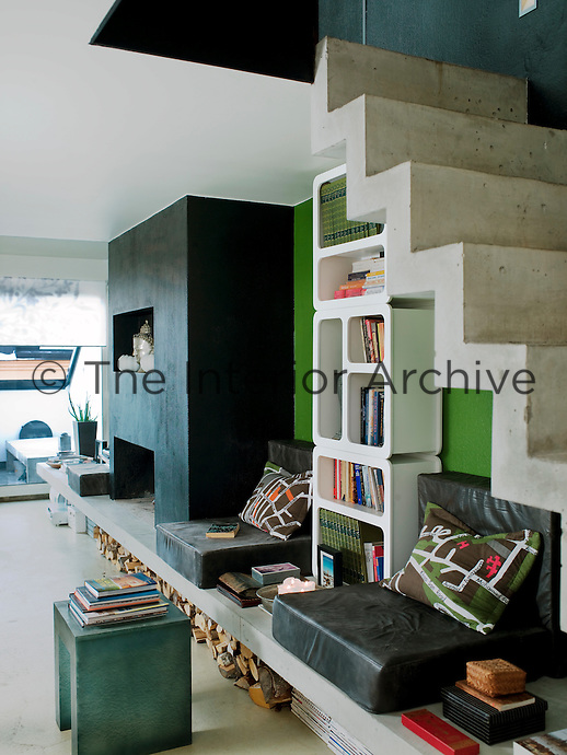 A moulded slab of concrete runs along one wall supporting the fireplace and the open staircase