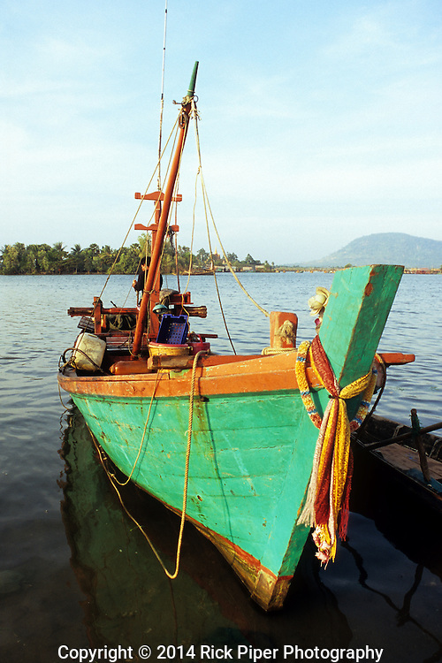 Prow of colourful traditional Cham fishing boat adorned with scarves, at dawn on the Sanke river, Kampot, Cambodia