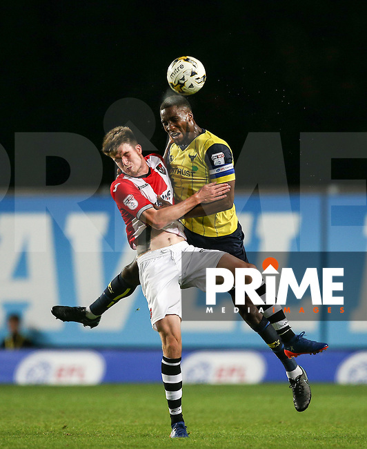 Cheyenne Dunkley of Oxford United clears from Liam McAlinden of Exeter City during the The Checkatrade Trophy match between Oxford United and Exeter City at the Kassam Stadium, Oxford, England on 30 August 2016. Photo by Andy Rowland / PRiME Media Images.