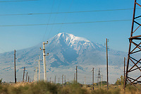 """Armenia. Ararat Province. Near the village of Araksavan. Electrical pylons. View on the Ararat Mountain which is a snow-capped and dormant compound volcano in the extreme east of Turkey. It consists of two major volcanic cones: Greater Ararat and Little Ararat. Greater Ararat is the highest peak in Turkey and the Armenian Highland with an elevation of 5,137 m; Little Ararat's elevation is 3,896 m. The Ararat massif is about 35 km wide at ground base. The """"mountains of Ararat"""" have been widely accepted in Christianity as the resting place of Noah's Ark, despite contention that Genesis 8:4 does not refer specifically to Mt. Ararat. It is the principal national symbol of Armenia and has been considered a sacred mountain by Armenians. It is featured prominently in Armenian literature and art and is an icon for Armenian irredentism.  3.10.2019 © 2019 Didier Ruef"""