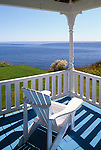 White adirondack chair on a porch overlooking the Atlantic Ocean, York, Maine, USA