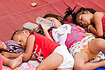 Apr. 19 2010 - BANGKOK, THAILAND: Red Shirt children sleep on mats on the ground in one of the Red Shirt protest sites. Hundreds of Thai soldiers, including reservists and front line units, and riot police moved into the Silom financial district Monday, not far from the red-shirts' main protest rally site, in Ratchaprasong. The heavy show of force is to prevent the Red Shirts from entering the Silom area. Many of soldiers were greeted as heros by workers in the area, who oppose the Red Shirts.   Photo by Jack Kurtz
