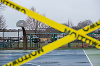 """A sign reading """"Basketball Closed Until Further Notice"""" and caution tape indicate that the basketball court at Town Field is closed in Belmont, Massachusetts, on Fri., March 20, 2020. Earlier in the week, the Town closed all parks, fields, courts, and playgrounds, as part of the lockdown response to the ongoing coronavirus COVID-19 pandemic."""