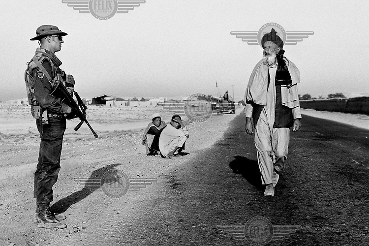 A Pashtun man walks past an Austrian soldier with the NATO-led International Security Assistance Force (ISAF) manning a checkpoint outside the Afghan capital Kabul on Monday,  July 1, 2002.
