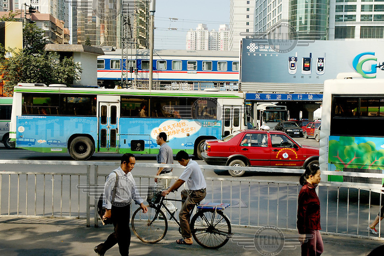 Street scene, with pedestrians, cyclist, bus, taxi and train passing, and a billboard for the China Unicom mobile telephone network.
