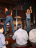 SINGAPORE, Asia, group of men watching female bartenders dancing on the bar at CU Bar.