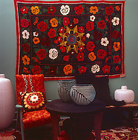 A floral pattern wall hanging in vibrant reds and orange hangs on the wall of a retro living room.