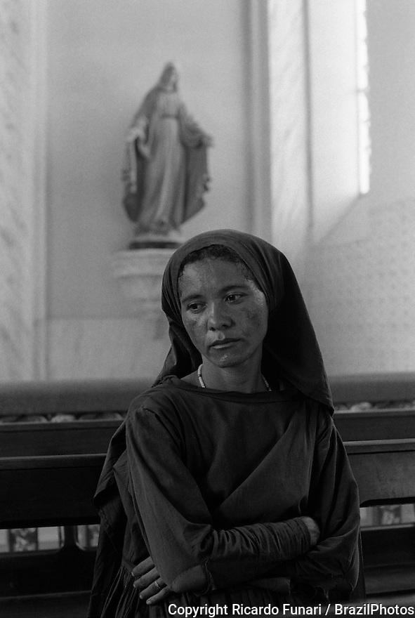 Woman in church, Catholicism. Pilgrimage to Juazeiro do Norte city in Ceara State, Northeastern Brazil.