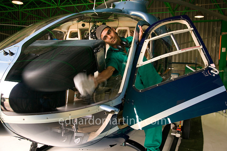 A Helicidade member of staff cleans an helicopter in one of their hangars.