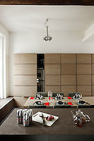 In the kitchen/dining area storage and appliances are hidden behind bespoke grooved cupboards designed by the architect; the tabletop has a eucalyptus wood finish and the work surface is brown granite