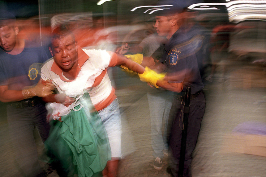Officers of Rio's Guardia Municipal drag an unwilling homeless man away from the subway station where he was sleeping. Though they are asked to voluntarily come to the shelter, those who refuse are forced.