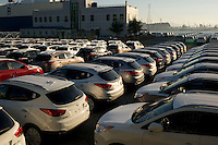 Hyundai cars are line-up on the port next to a car transporter in Ulsan South Korea. The Ulsan plant is the world's largest automobile plant which has its own port where up to three, 50,000-ton ships can anchor simultaneously..