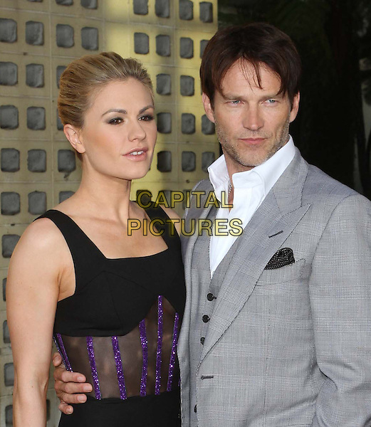 "Anna Paquin & Stephen Moyer.HBO's ""True Blood"" Season 4 Premiere  Held At The ArcLight Cinemas Cinerama Dome, Hollywood, California, USA..June 21st, 2011.half length black dress mesh see thru through clutch bag bracelet purple striped stripes sparkly midriff cut out sleeveless grey gray suit husband wife married arm around hand in pocket stubble facial hair waistcoat white shirt .CAP/ADM/KB.©Kevan Brooks/AdMedia/Capital Pictures."