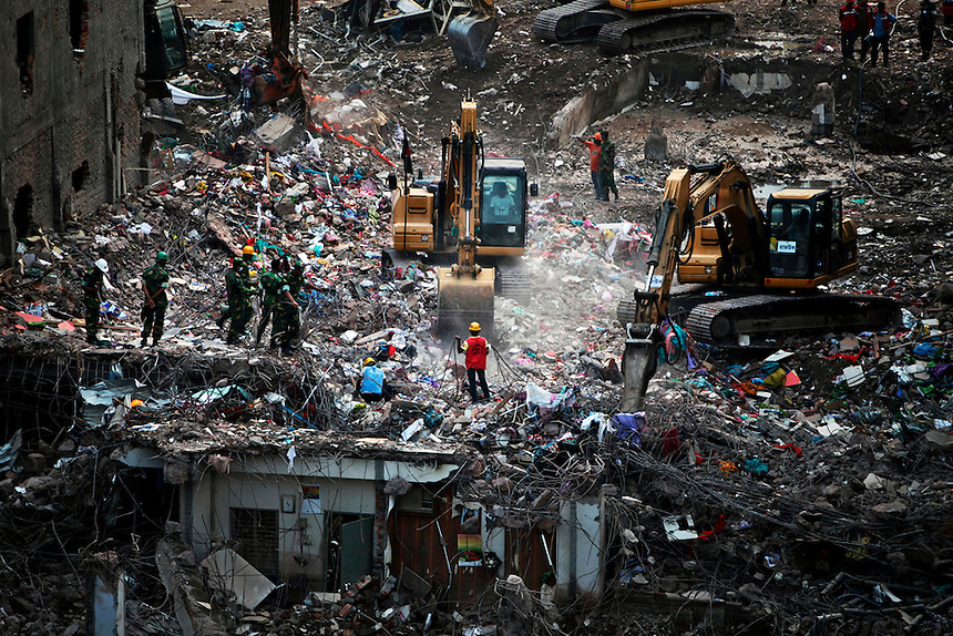 In this Sunday, May 12, 2013 file photo, Bangladeshi rescuers use heavy machinery to clear rubble of a garment factory building that collapsed on April 24 as they continue searching for bodies in Savar, near Dhaka, Bangladesh.
