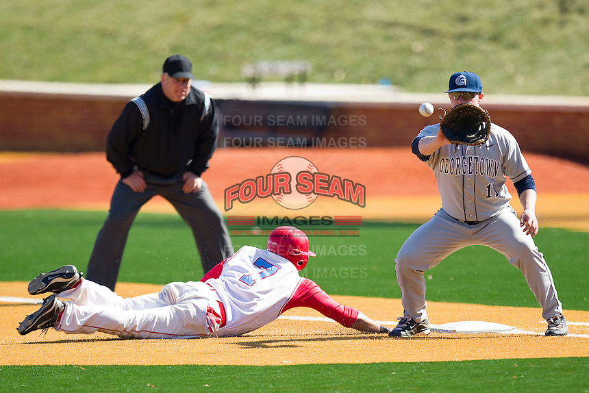 First baseman Dan Capeless #11 of the Georgetown Hoyas waits for a throw as Mike Rizzuto #7 of the Delaware State Hornets dives back to the bag at Gene Hooks Field on February 26, 2011 in Winston-Salem, North Carolina.  Photo by Brian Westerholt / Four Seam Images