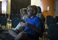 NWA Democrat-Gazette/CHARLIE KAIJO Jonah Parrish, 10, of Rogers eats a snack while watching Muppets From Space during a children's Monday movie screening, Monday, June 10, 2019 at the Rogers Public Library in Rogers.<br />