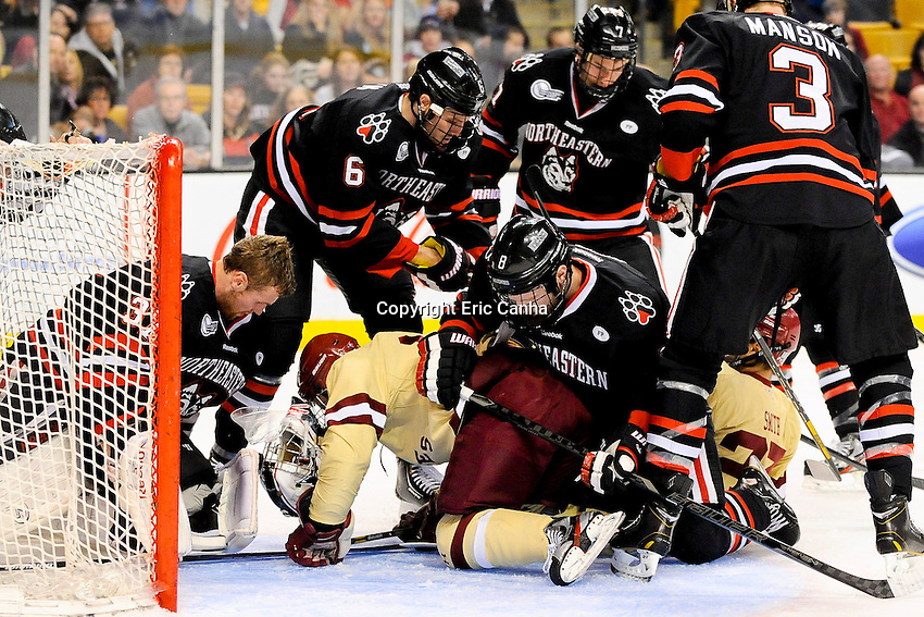 Northeastern University Huskies goalie Chris Rawlings (37) loses his helmet as Boston College forward Brooks Dyroff (14) crashes into him on a goal attempt during the championship round of the Beanpot Tournament hockey between Boston College and Northeastern University held at TD Garden in Boston Massachusetts.  Eric Canha/CSM