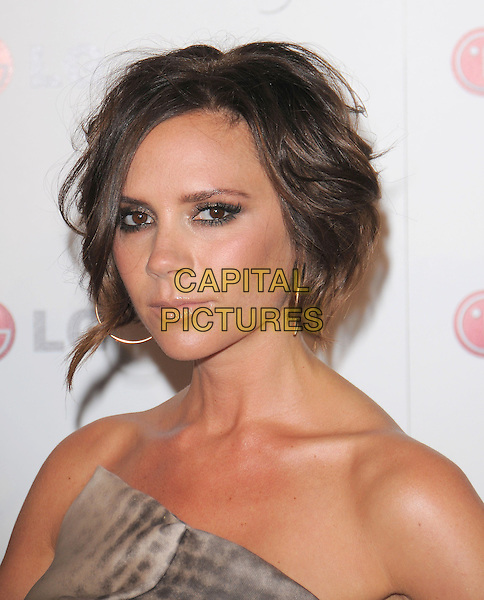 VICTORIA BECKHAM.wearing her own design.at A Night of Fashion & Technology with LG Mobile Phones held at SoHo House in West Hollywood, California, USA, .May 24th 2010..portrait headshot bob wavy hair make-up brown digital print strapless grey gray  beige asymmetric  gold hoop earrings             .CAP/RKE/DVS.©DVS/RockinExposures/Capital Pictures.