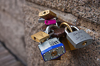 "Worried that it will get away, people have been putting padlocks on the Brooklyn Bridge.  Okay, actually, a trend of late is apparently for tourists (and lovers?) to attach locks onto various parts of the Brooklyn Bridge, along with the date of their visit.  This picture shows a cluster of the locks (nearly a dozen) attached to a single ring protruding from the brick of the Brooklyn Bridge.  One lock reads ""Bonnie & Jack 2012""."