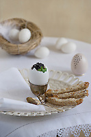 Detail of an Easter breakfast of a boiled egg topped with caviar accompanied by toasted soldiers