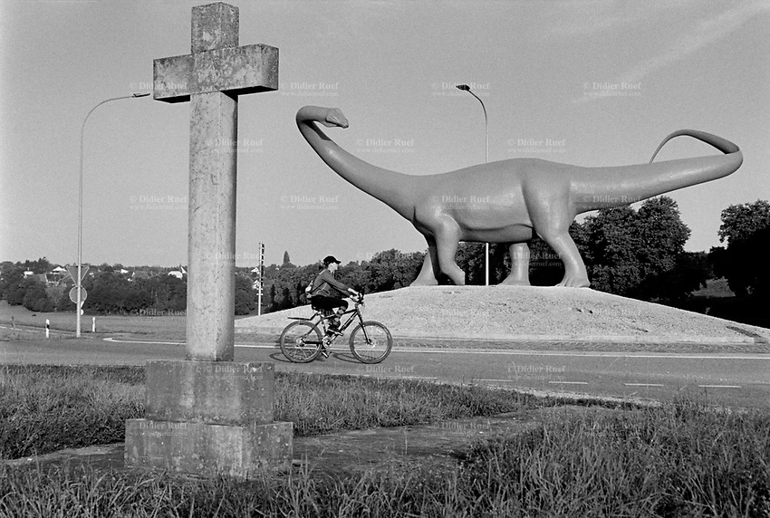 Switzerland. Canton Jura. Porrentruy. A life-size prehistoric diplodocus, created by the sculptor Hervé Bénard, on a roundabout at the town's west exit. A teenage woman rides her bicycle in the early morning. An antique catholic stone cross stands on the side of the roundabout..15.08.2017 © 2017 Didier Ruef