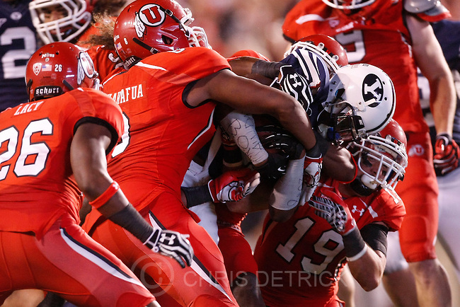 Chris Detrick  |  The Salt Lake Tribune.Brigham Young Cougars running back Jamaal Williams (21) is tackled by Utah Utes defensive back Ryan Lacy (26) Utah Utes defensive tackle Viliseni Fauonuku (98) and Utah Utes defensive back Quade Chappuis (19) during the first half of against BYU at Rice-Eccles Stadium Saturday September 15, 2012.  The score is 7-7 at halftime.