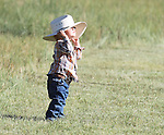 Nolan Gorman, 2, pulls tight his cowboy hat as he and his family prepare to load into the family hay wagon during the Cheyenne Frontier Days cattle drive on Horse Creek Road Sunday morning. Michael Smith/staff